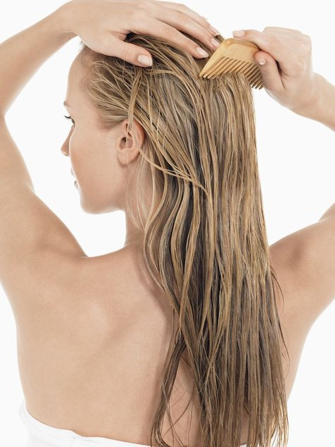 Devojka češlja mokru kosu drvenim češljom